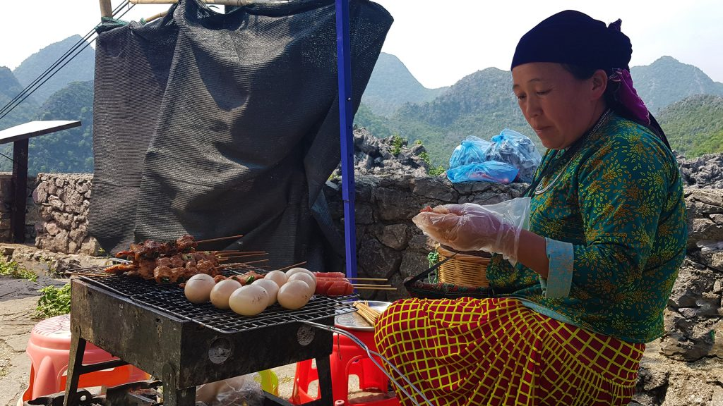 local woman cooking meat and eggs up in Dong Van